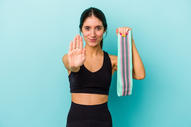 Jovem mulher desportiva, caucasiana, segurando elásticos isolados em um fundo azul em pé com a mão estendida, mostrando o sinal de stop, impedindo-o.