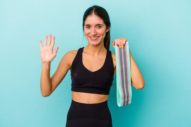 Jovem mulher desportiva, caucasiana, segurando elásticos isolados no fundo azul, sorrindo alegre mostrando o número cinco com os dedos.