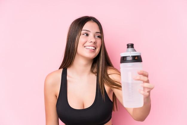 Jovem mulher desportiva caucasiana segurando uma garrafa de água