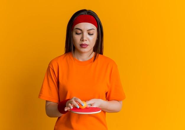 Jovem mulher desportiva com bandana e pulseiras segurando e olhando para uma raquete de pingue-pongue com uma bola tocando a bola