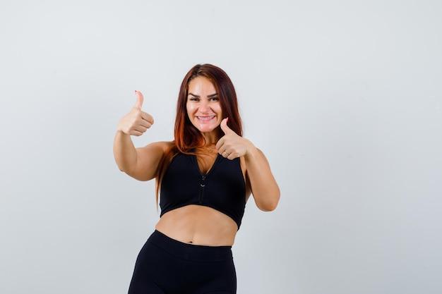 Jovem mulher desportiva com cabelo comprido aparecendo os polegares para cima