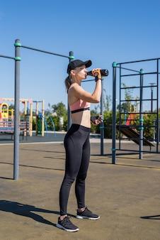 Jovem mulher desportiva com luvas desportivas a beber água no campo desportivo