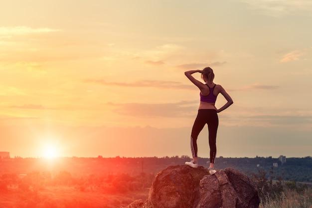 Jovem mulher desportiva com os braços levantados ao pôr do sol