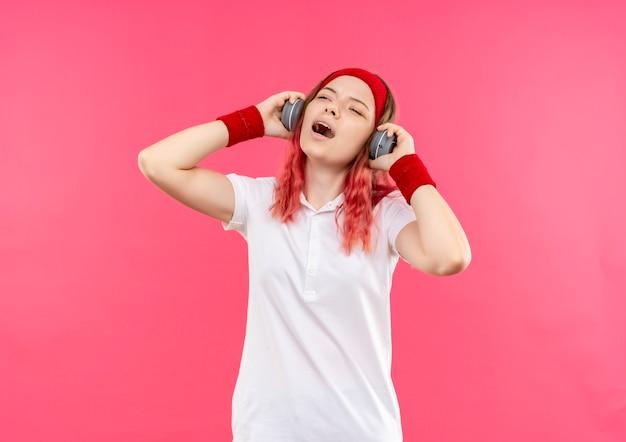 Jovem mulher desportiva com uma bandana na cabeça e fones de ouvido, curtindo sua música favorita e se sentindo feliz cantando uma música em pé sobre a parede rosa