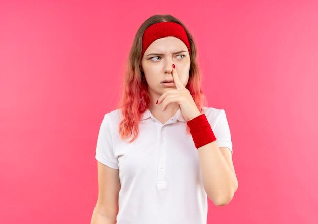 Jovem mulher desportiva com uma bandana olhando para o lado tocando o nariz com uma expressão pensativa no rosto em pé sobre a parede rosa