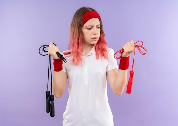 Jovem mulher desportiva com uma bandana segurando cordas de pular, confusa em pé sobre a parede roxa