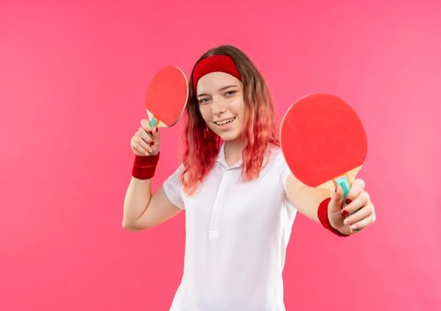 Jovem mulher desportiva com uma bandana segurando duas raquetes de tênis de mesa e sorrindo com uma cara feliz em pé sobre a parede rosa