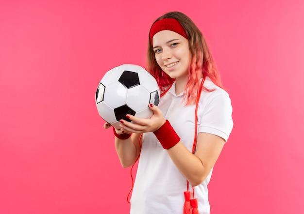 Jovem mulher desportiva com uma bandana segurando uma bola de futebol com um sorriso no rosto em pé sobre a parede rosa