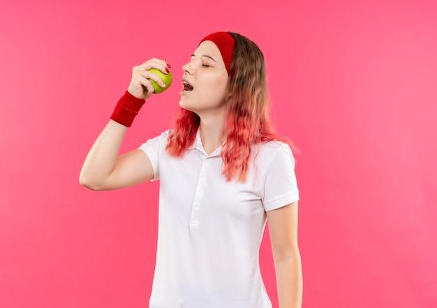 Jovem mulher desportiva com uma bandana segurando uma maçã verde indo morder em pé sobre a parede rosa