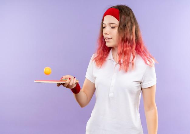 Jovem mulher desportiva com uma bandana segurando uma raquete de tênis de mesa e bolas, brincando com um sorriso no rosto em pé sobre a parede roxa