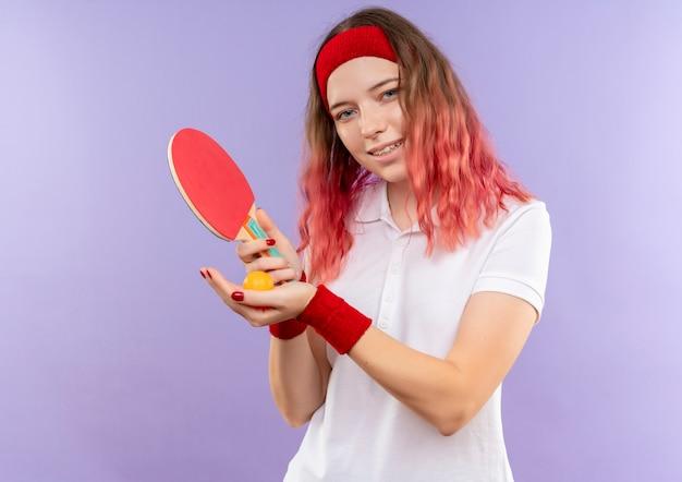 Jovem mulher desportiva com uma bandana segurando uma raquete de tênis de mesa e bolas com um sorriso no rosto em pé sobre a parede roxa