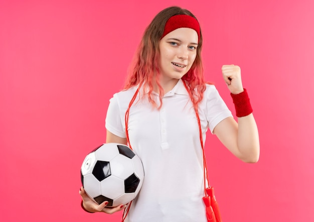 Jovem mulher desportiva com uma faixa na cabeça, segurando uma bola de futebol com o punho cerrado, feliz e saindo em pé sobre a parede rosa