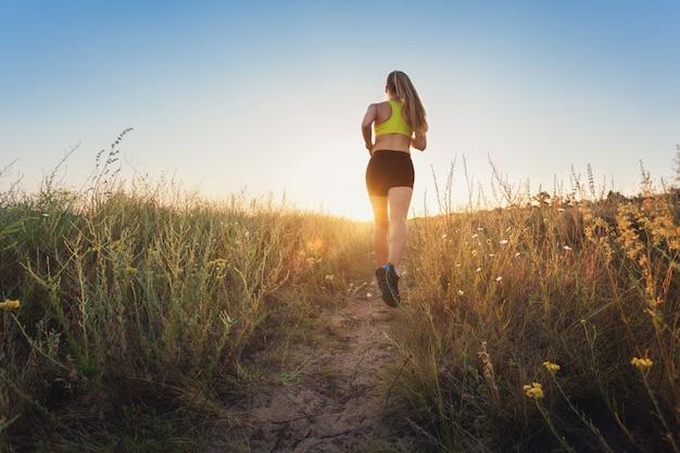 Jovem mulher desportiva correndo em uma estrada rural ao pôr do sol