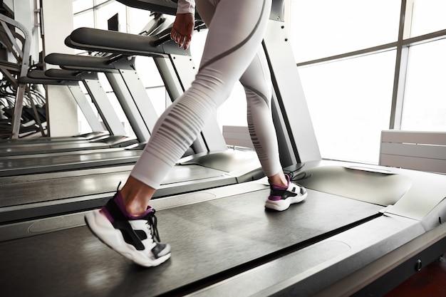 Jovem mulher desportiva correndo na esteira. treino de ginásio