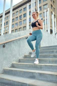 Jovem mulher desportiva correndo nas escadas da cidade