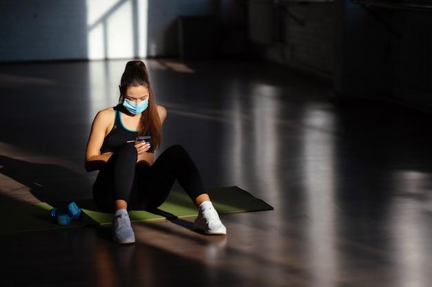 Jovem mulher desportiva depois de praticar ioga, pausa para fazer exercícios e relaxar no tapete de ioga