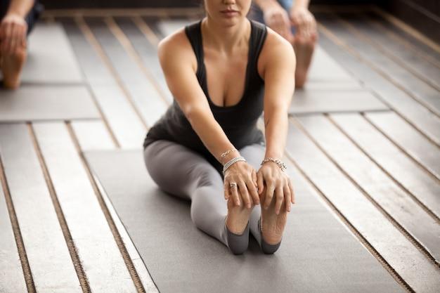 Jovem mulher desportiva em paschimottanasana pose