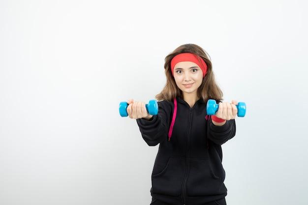Jovem mulher desportiva em pé e segurando halteres azuis.