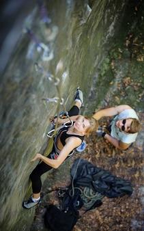 Jovem mulher desportiva escalada com carabinas e corda
