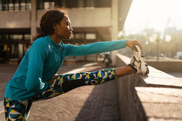 Jovem mulher desportiva fazendo alongamento ao ar livre em um dia ensolarado