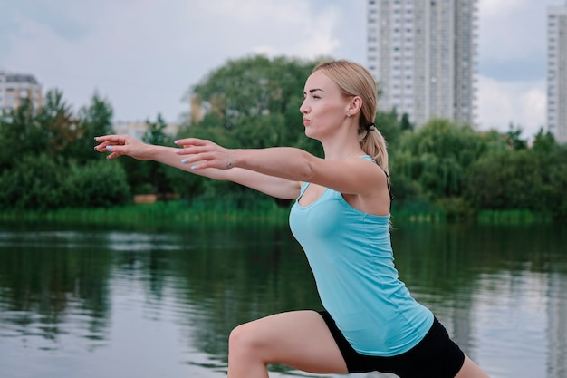 Jovem mulher desportiva fazendo esportes ao ar livre, exercícios de fitness.