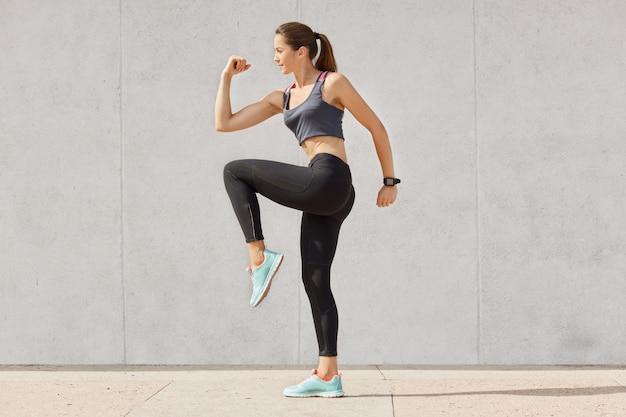 Jovem mulher desportiva fazendo exercício contra cinza