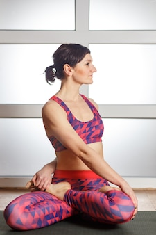 Jovem mulher desportiva fazendo exercício padmasana