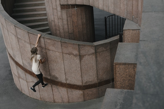 Jovem mulher desportiva fazendo parkour na cidade. a garota está envolvida em freerunning.