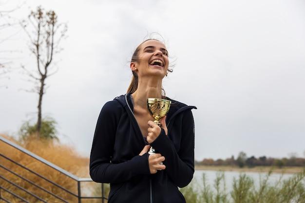Jovem mulher desportiva feliz segurando o troféu de ouro