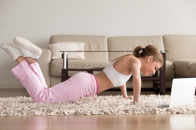 Jovem mulher desportiva malhando em casa, fazendo flexões