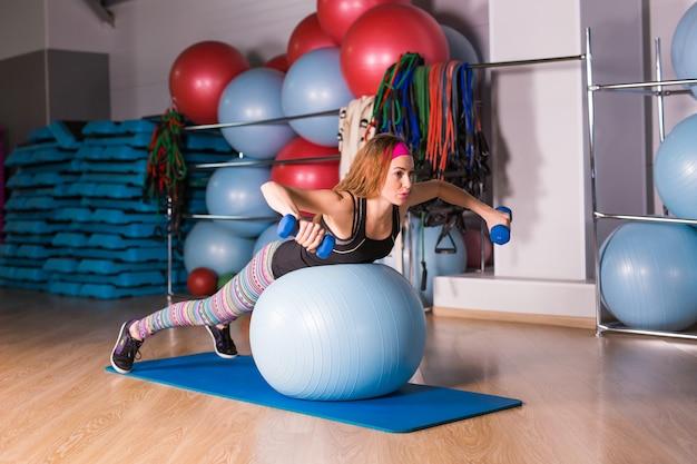 Jovem mulher desportiva no ginásio fazendo exercícios de fitness com bola azul