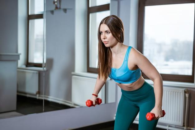 Jovem mulher desportiva praticando fitness com halteres no ginásio