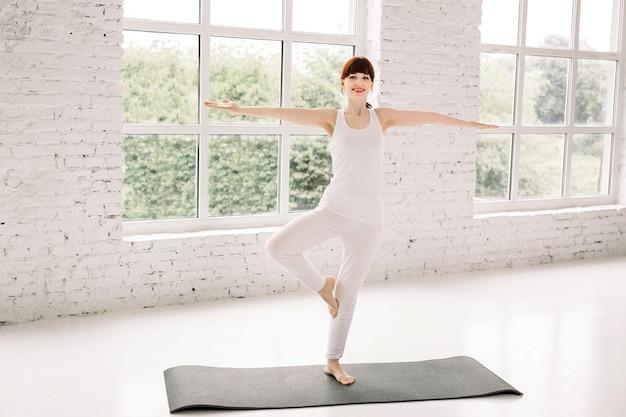 Jovem mulher desportiva praticando ioga em casa, em pé no exercício vrksasana, pose de árvore, malhando, vestindo roupas esportivas brancas, comprimento total interior
