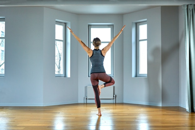 Jovem mulher desportiva praticando ioga, malhando, vestindo roupas esportivas, calças e top, close-up interno, estúdio de ioga