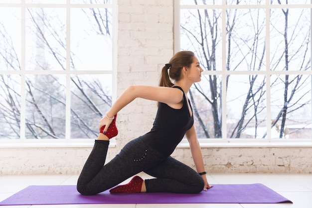 Jovem mulher desportiva praticando ioga perto da janela