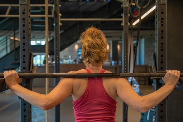 Jovem mulher desportiva reforça com halteres no ginásio