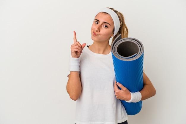 Jovem mulher desportiva segurando um tapete mostrando o número um com o dedo.