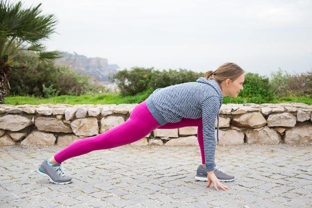 Jovem mulher desportiva séria que estica as pernas ao ar livre