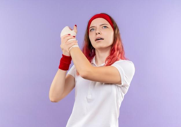 Jovem mulher desportiva tocando o pulso enfaixado sentindo dor, olhando para cima em pé sobre a parede roxa