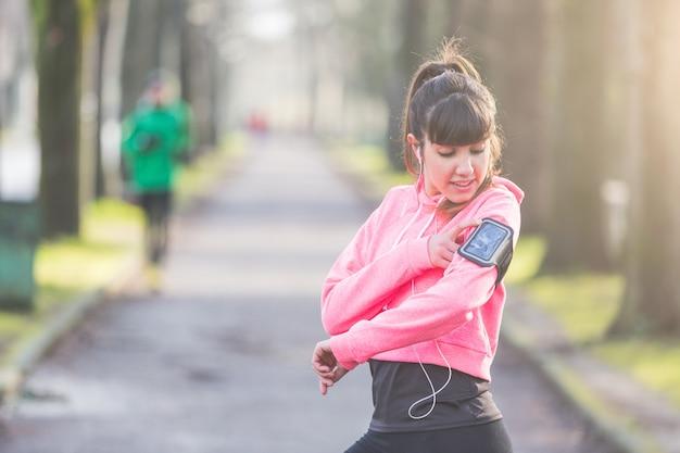 Jovem mulher desportiva, verificando o telefone inteligente durante treino