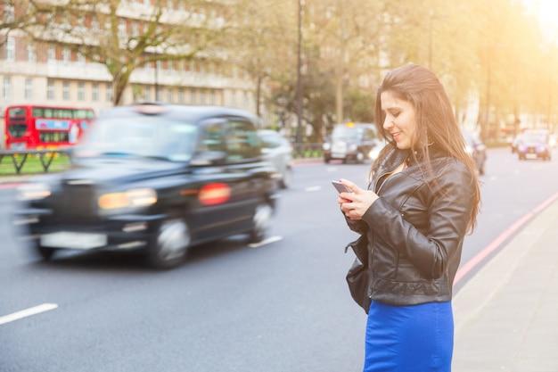 Jovem, mulher, digitando em seu telefone inteligente por uma estrada movimentada em londres