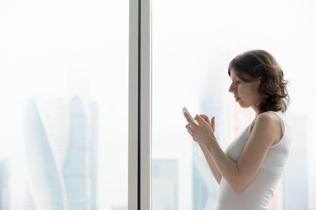 Jovem, mulher, digitando, smartphone, mensagem