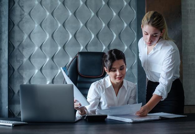 Jovem mulher diretora de negócios sentada na mesa do escritório com documentos, processo de trabalho, reunião de negócios, trabalhando com um colega, resolvendo tarefas de negócios, conceito coletivo de escritório