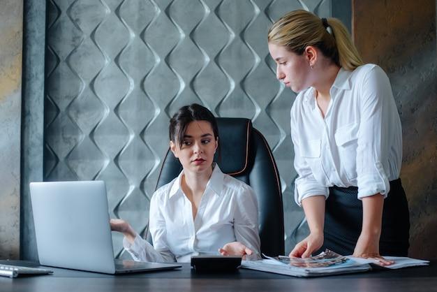 Jovem mulher diretora de negócios sentada na mesa do escritório descontente processo de trabalho reunião de negócios trabalhando com colega resolvendo tarefas de negócios conceito coletivo de escritório