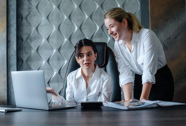 Jovem mulher diretora de negócios sentada na mesa do escritório, processo de trabalho, reunião de negócios, trabalhando com um colega, resolvendo tarefas de negócios conceito coletivo de escritório