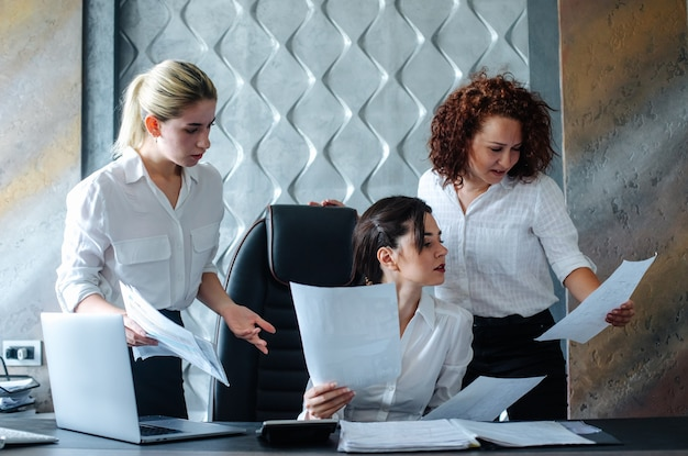 Jovem mulher diretora de negócios sentada na mesa do escritório, usando o computador laptop, processo de trabalho, reunião de negócios trabalhando com colegas, resolvendo tarefas de negócios conceito coletivo de escritório