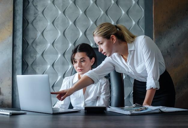 Jovem mulher diretora de negócios sentada na mesa do escritório, usando o computador laptop, processo de trabalho, reunião de negócios, trabalhando com um colega, resolvendo tarefas de negócios, conceito coletivo de escritório