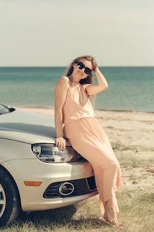 Jovem mulher dirige um carro na praia