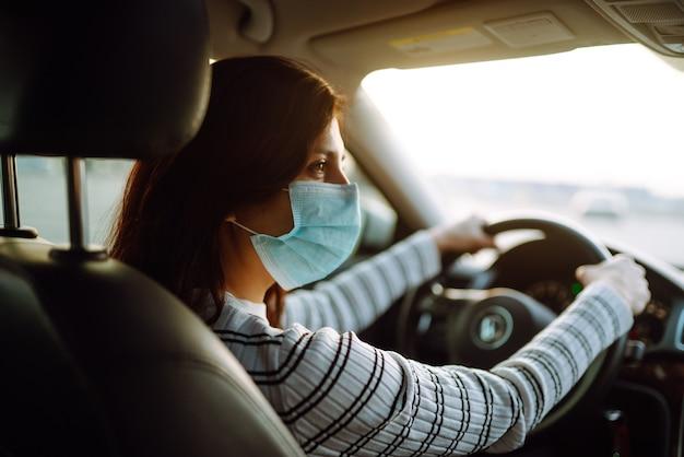 Jovem mulher dirigindo carro com máscara protetora no rosto. isolamento de transporte.