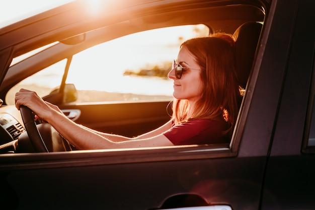 Jovem mulher dirigindo um carro ao pôr do sol. conceito de viagens